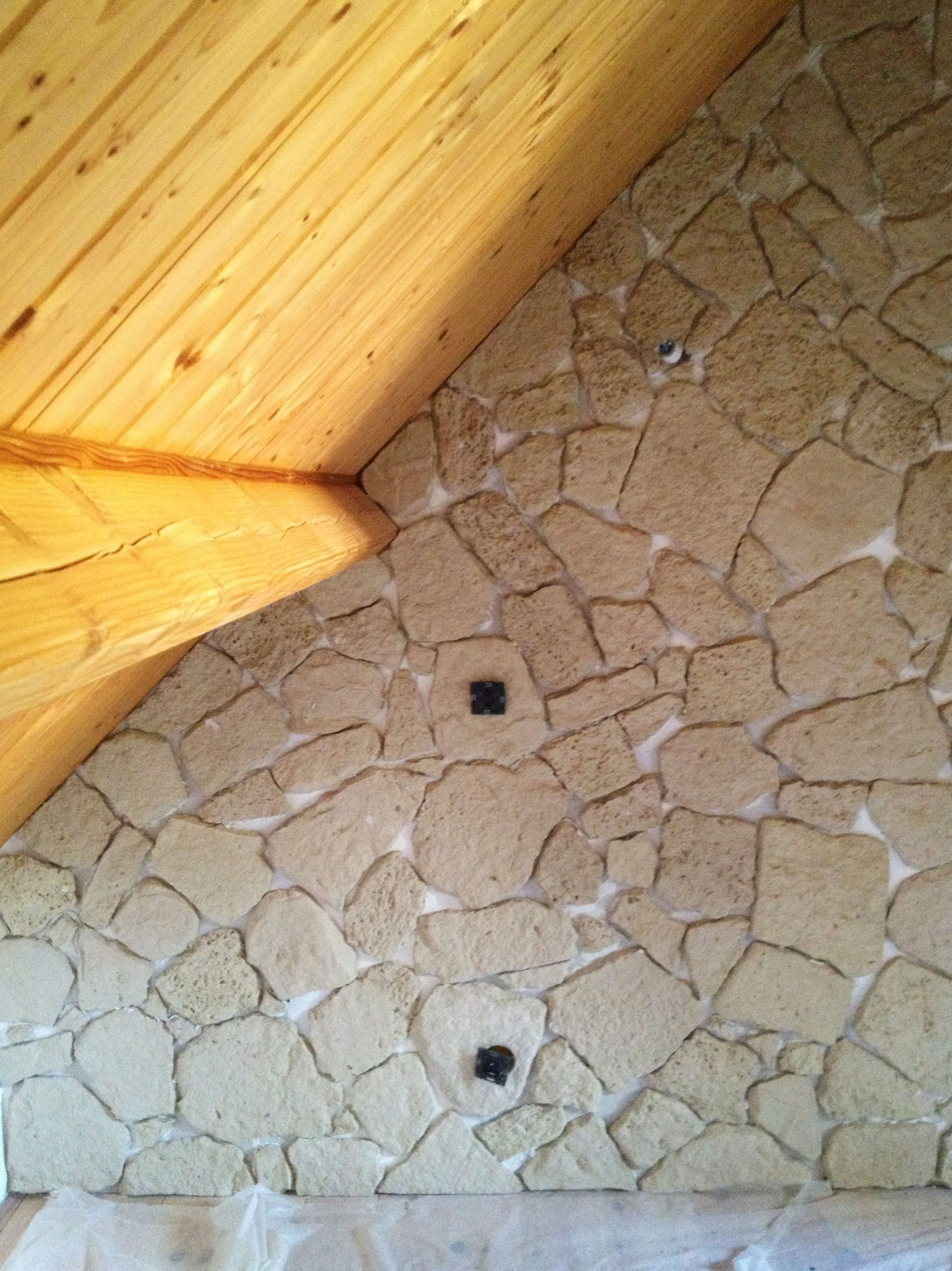dans cette chambre sous comble, rénovation avec un mur en pierre